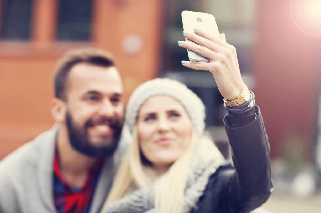 Пара на свидании фотографируется на телефон