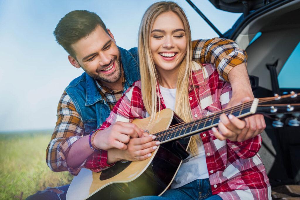 Девушка и парень играют на гитаре