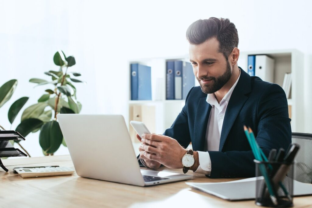 Красивый парень в офисе за ноутбуком