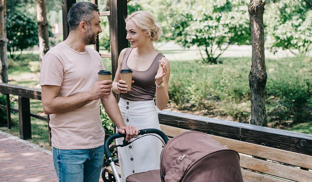 молодые родители на прогулке с коляской